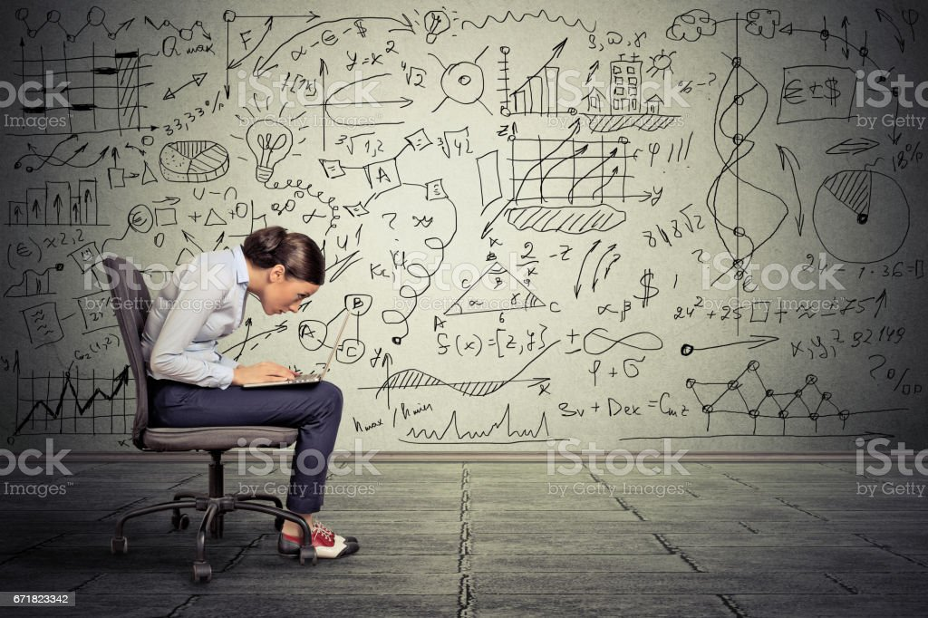 Young serious woman working on computer sitting on chair stock photo
