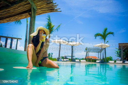 883117662 istock photo young sexy and attractive exotic Asian woman in bikini and Summer hat drinking juice in paradise swimming pool resort bar smiling happy enjoying luxury holidays trip in tropical island 1094734042
