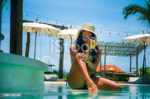 883117662 istock photo young sexy and attractive exotic Asian woman in bikini and Summer hat drinking juice in paradise swimming pool resort bar smiling happy enjoying luxury holidays trip in tropical island 1094735150