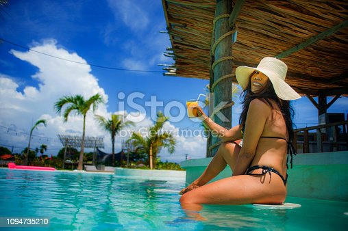 883117662 istock photo young sexy and attractive exotic Asian woman in bikini and Summer hat drinking juice in paradise swimming pool resort bar smiling happy enjoying luxury holidays trip in tropical island 1094735210