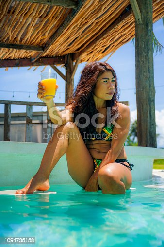 883117662 istock photo young sexy and attractive exotic Asian woman in bikini drinking juice in paradise swimming pool resort bar smiling happy enjoying luxury holidays trip in tropical island 1094735158