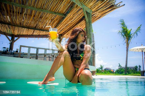 883117662 istock photo young sexy and attractive exotic Asian woman in bikini drinking juice in paradise swimming pool resort bar smiling happy enjoying luxury holidays trip in tropical island 1094735194