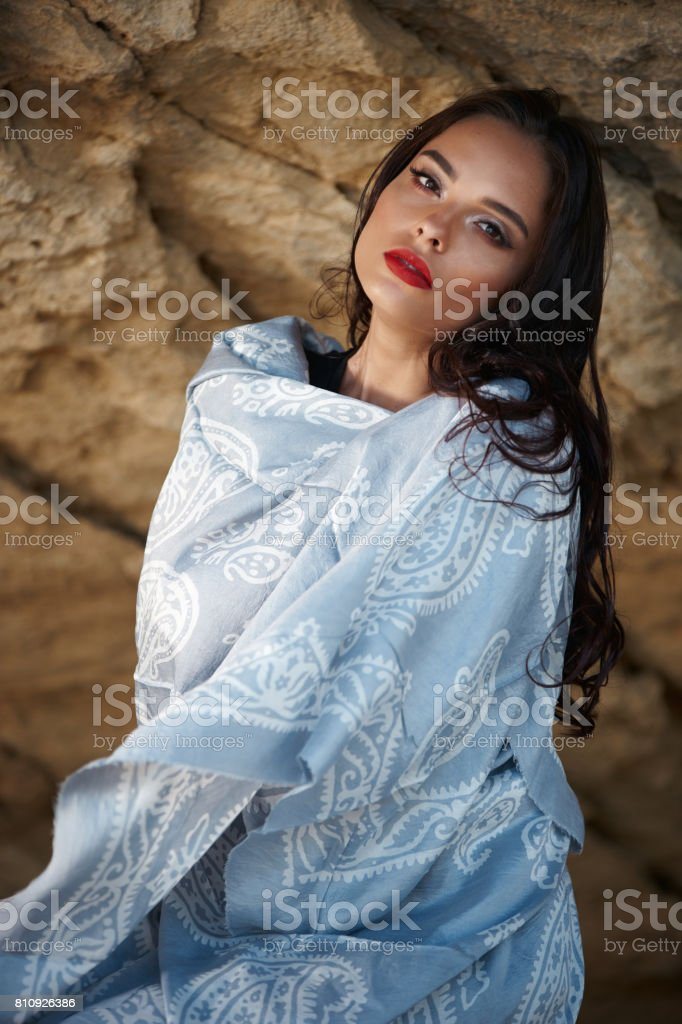 Young sexy oriental lady with colorful scarf posing in mountain. stock photo