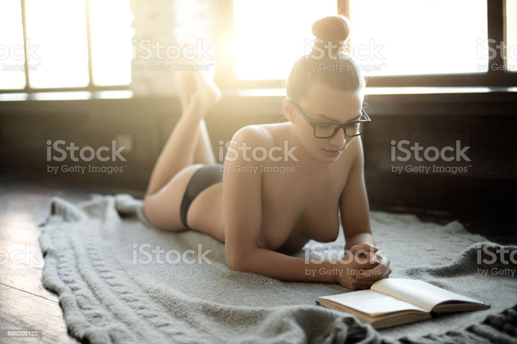 young sexy beauty woman lie home on floor and read book stock photo