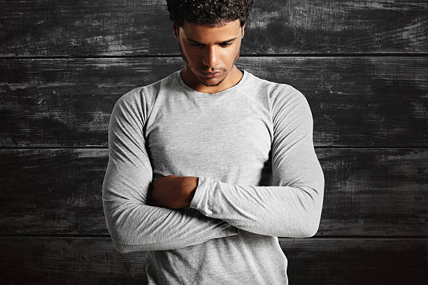 Young sexy black model wearing light gray longsleeve t-shirt Thoughtful-looking fit dark-skinned model wearing a plain cotton light gray t-shirt with his arms crossed on the background of a black painted wooden wall. long sleeved stock pictures, royalty-free photos & images