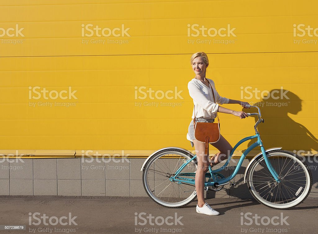 Young sexy blonde girl is standing near the vintage bicycle stock photo