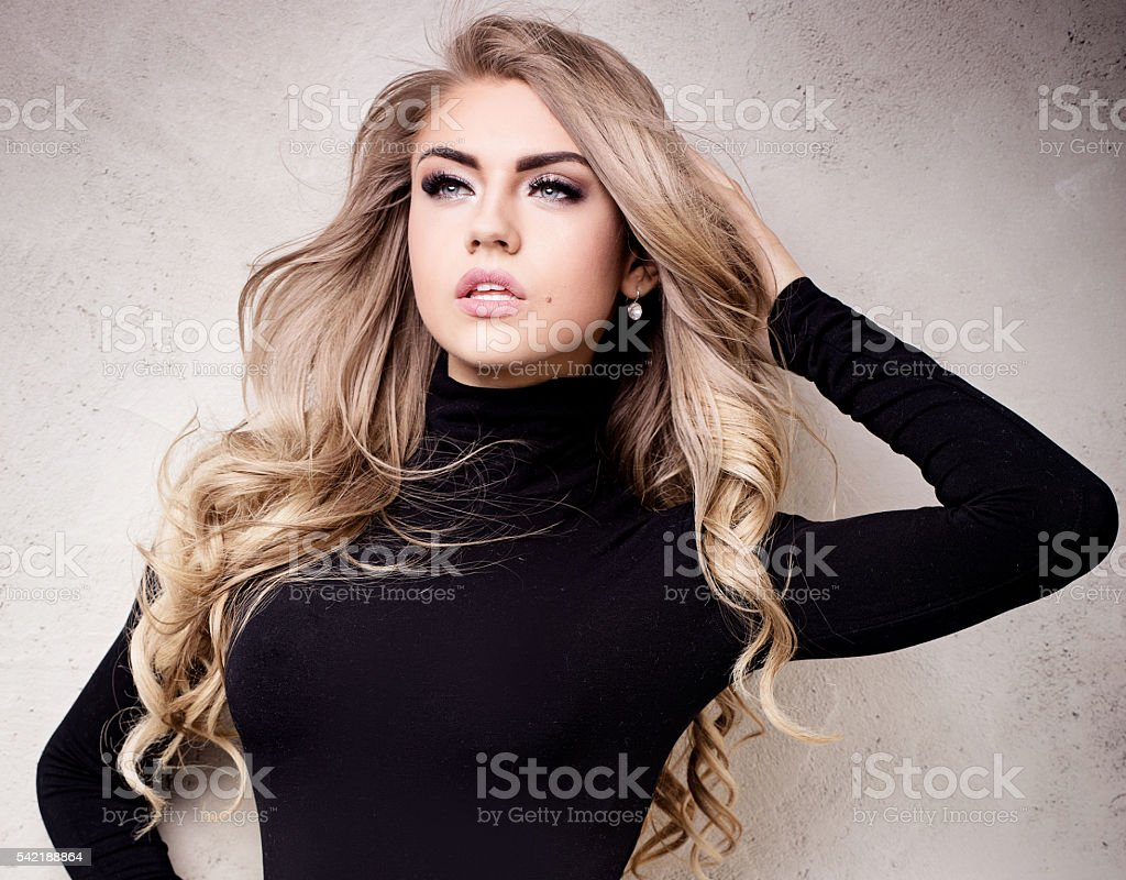 Young sexy blonde girl posing in studio. stock photo