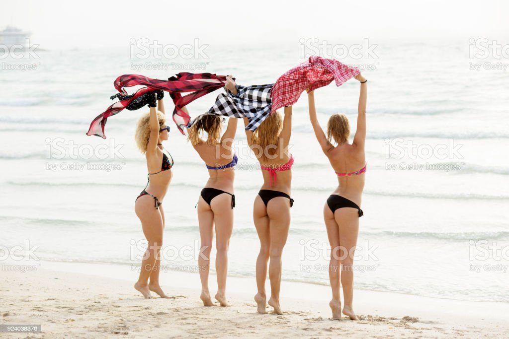 Young sexy girlfriends in bikinis waving their plaid shirts on the beach. Summertime girl fun. stock photo