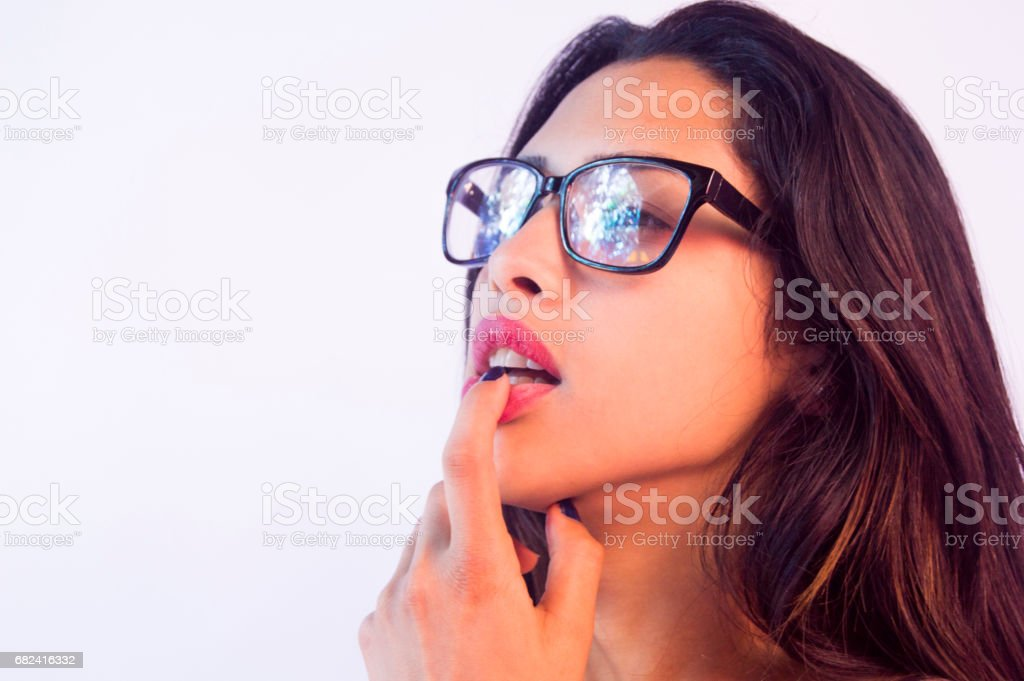 young sexy girl,reflection on glasses,one finger on lip lookin left side,close up royalty-free stock photo