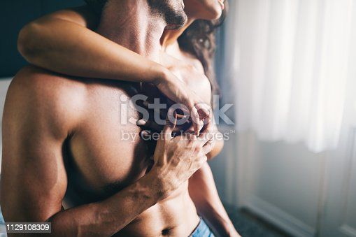 Young sexy hot couple in love hugging and kissing. Beautiful woman and handsome muscular man close to each other in erotic pose.