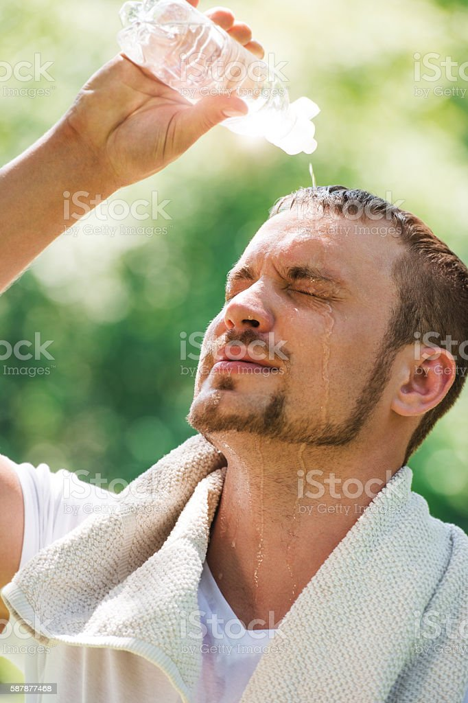Young sexy male athlete is refreshing himself with water stock photo