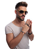 young sexy man in sunglasses is praying on white background