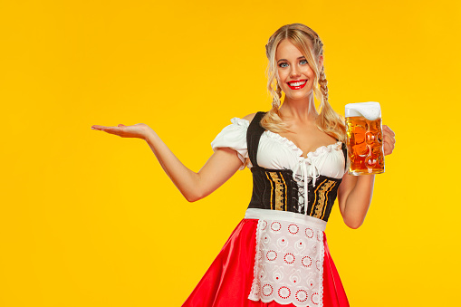 Young sexy Oktoberfest girl waitress, wearing a traditional Bavarian or german dirndl, serving big beer mug with drink isolated on yellow background. Woman pointing to looking left.