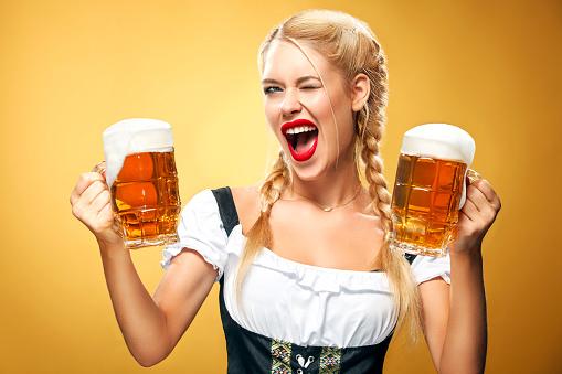 Young sexy Oktoberfest waitress, wearing a traditional Bavarian dress, serving