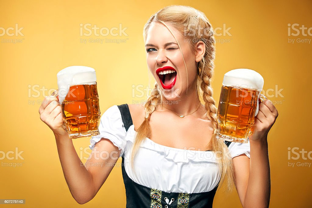 Young sexy Oktoberfest waitress, wearing a traditional Bavarian dress, serving - Photo