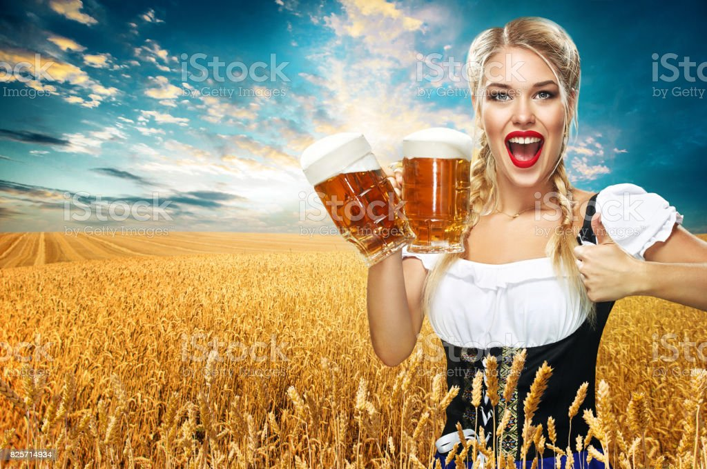 Young sexy Oktoberfest waitress, wearing a traditional Bavarian dress, serving big beer mugs on blue background. stock photo