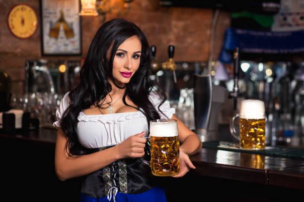 junge sexy oktoberfest kellnerin, eine bayerische tracht tragen mit großer bierkrug - arbeit in münchen stock-fotos und bilder