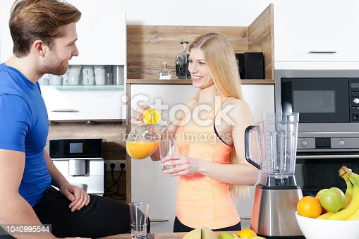 istock young sexy sporty couple is making a smoothy 1040995544