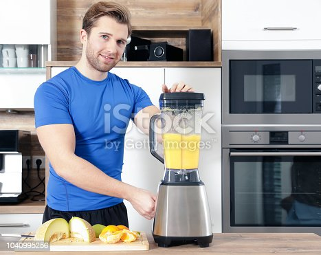 istock young sexy sporty man is making a smoothy 1040995256