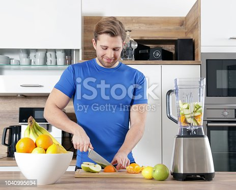 istock young sexy sporty man is making a smoothy 1040995694