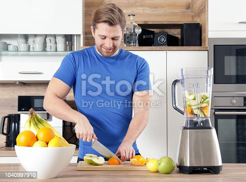 istock young sexy sporty man is making a smoothy 1040997910