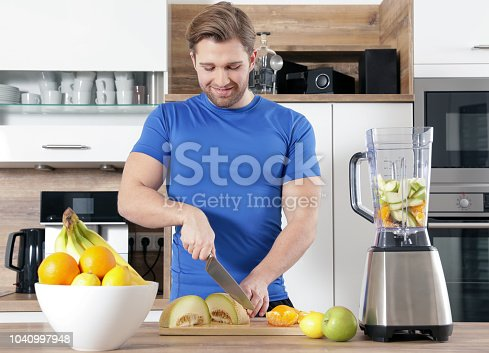 istock young sexy sporty man is making a smoothy 1040997948