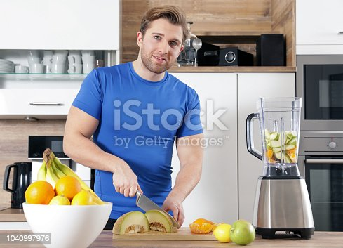 istock young sexy sporty man is making a smoothy 1040997976