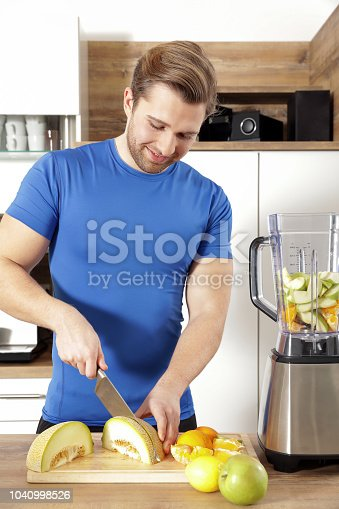 istock young sexy sporty man is making a smoothy 1040998526