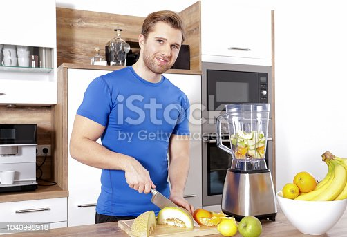 istock young sexy sporty man is making a smoothy 1040998918