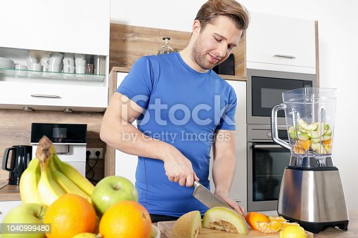 istock young sexy sporty man is making a smoothy 1040999480