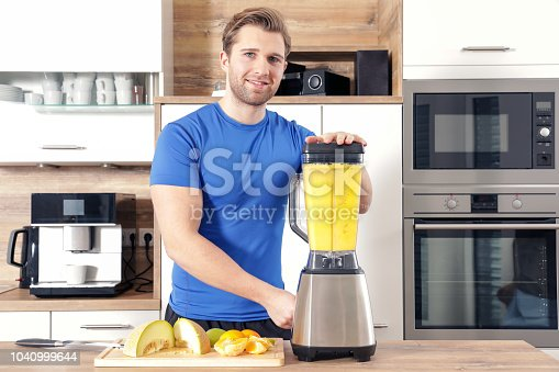 istock young sexy sporty man is making a smoothy 1040999644