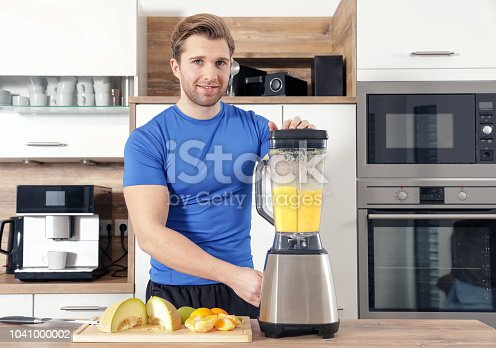 istock young sexy sporty man is making a smoothy 1041000002
