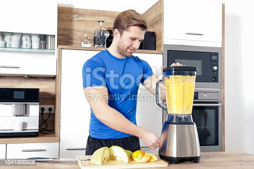 istock young sexy sporty man is making a smoothy 1041000308