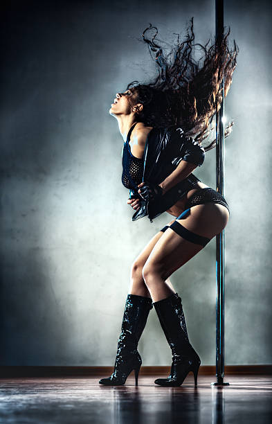 A young sexy woman posing seductively against a pole stock photo