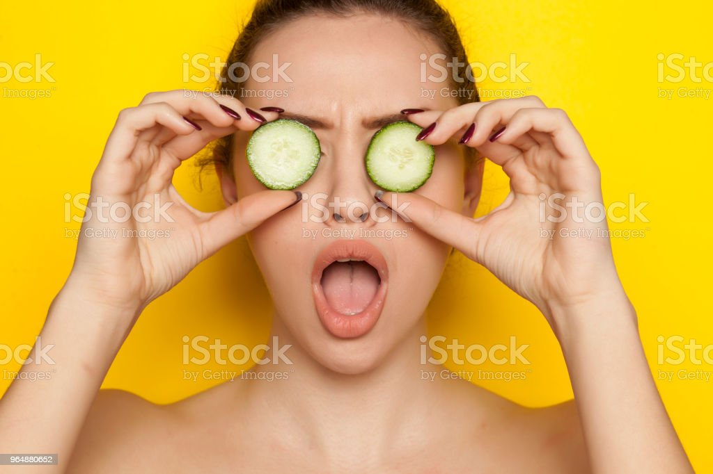 Young sexy woman posing with slices of cucumber on her face on yellow background royalty-free stock photo