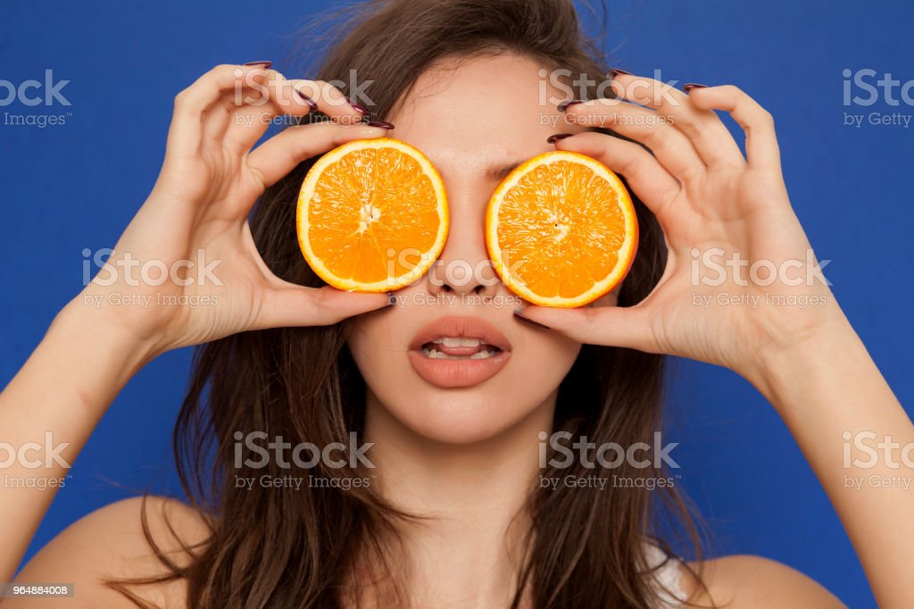 Young sexy woman posing with slices of oranges on her face on blue background royalty-free stock photo