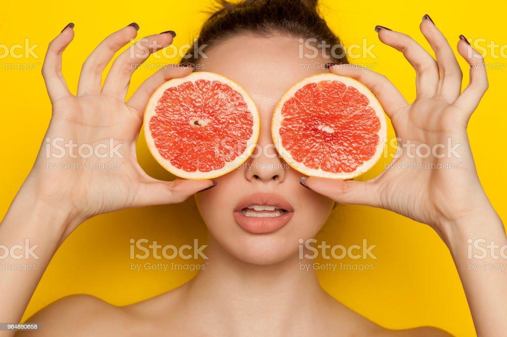 年輕性感的女人擺在她的臉上的紅色柚子片黃色背景 - 免版稅一個人圖庫照片