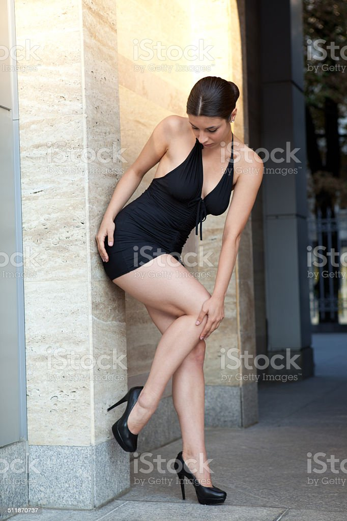 Young sexy woman with black dress posing outdoor stock photo