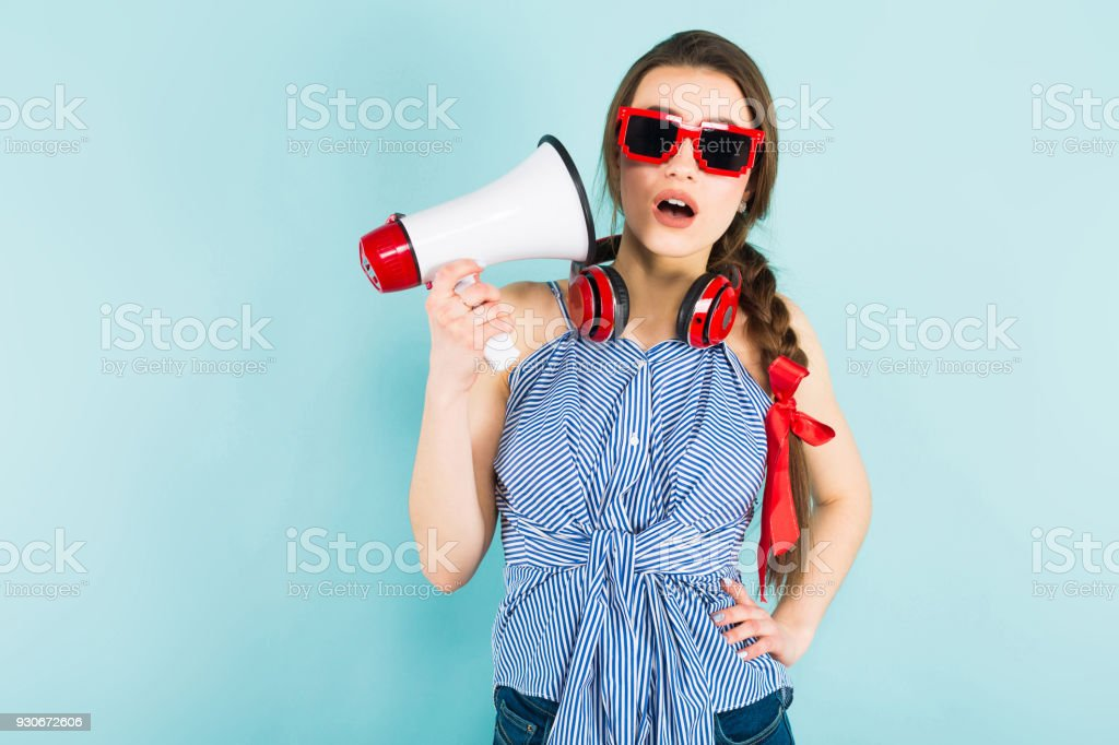 Young sexy woman with headphones and loudspeaker - Stock image .