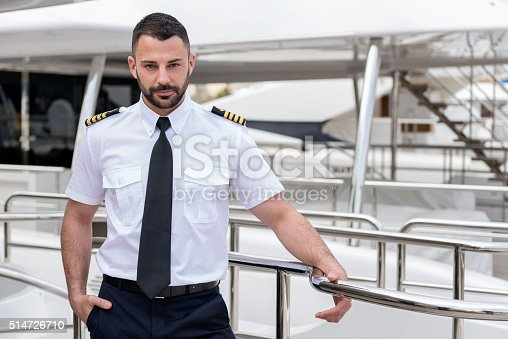Horizontal color image of young ship captain posing on boat deck of luxury yacht, holding railing with hand in pocket and proudly looking at camera. Attractive men wearing elegant uniform.