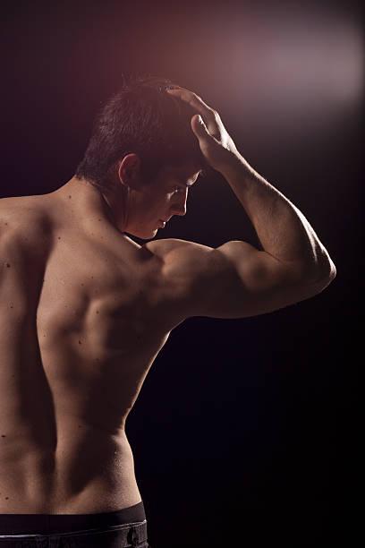 young shirtless adult on black background. - mit muskelkater trainieren stock-fotos und bilder