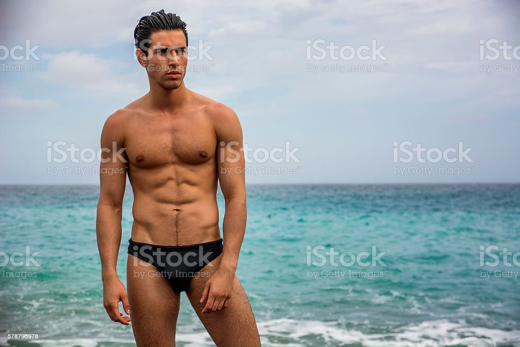 Young shirtless athletic man standing in water by ocean shore stock photo