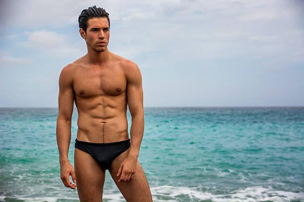 sportlich junger nackter oberkörper mann stehend im wasser von ocean shore - sexsymbol stock-fotos und bilder
