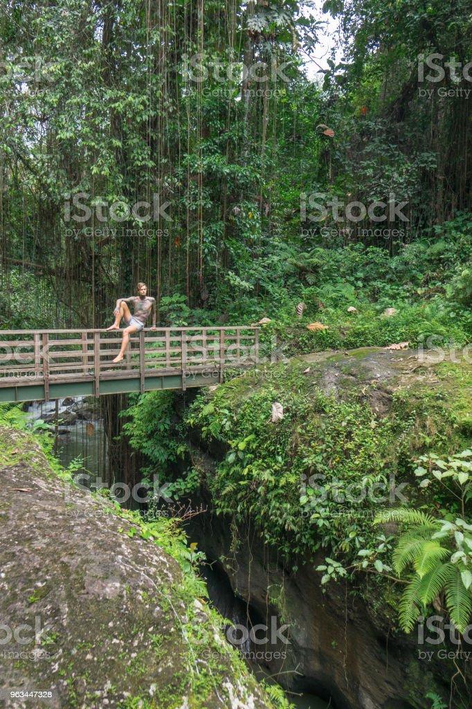 jeunes torse nu tatoué un homme assis sur le pont avec des plantes vertes autour, bali, Indonésie - Photo de Activités de week-end libre de droits