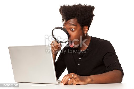 istock Young shocked african-american man looking trough magnifying glas on his laptop computer on white background 1049251566