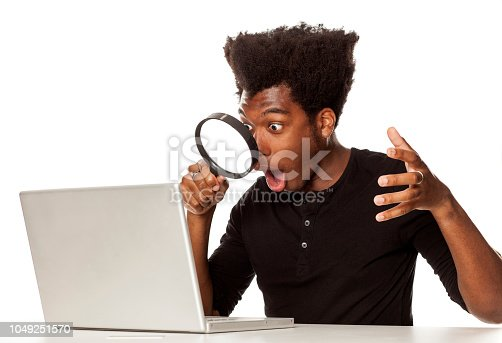 istock Young shocked african-american man looking trough magnifying glas on his laptop computer on white background 1049251570