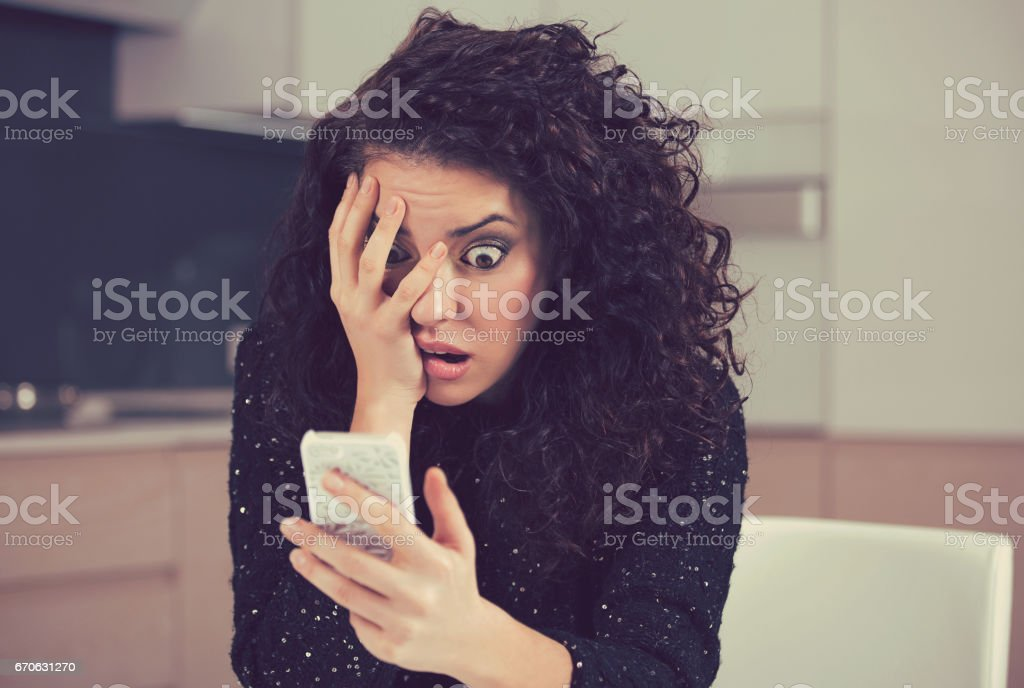 Young shocked anxious woman looking at phone seeing bad news photos message with scared emotion on face stock photo