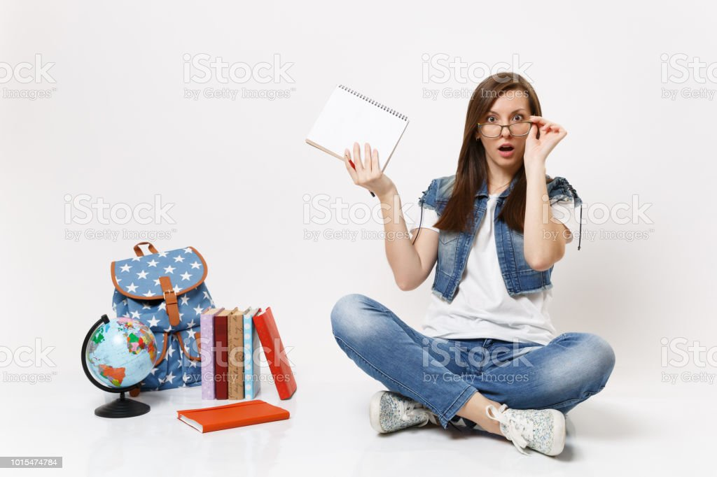 Young shocked bewildered woman student keeping hand on glasses hold pencil notebook sitting near globe backpack, school books isolated on white background. Education in high school university college. stock photo