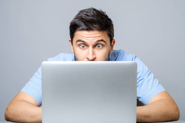 Young shocked man dressed in blue shirt while using laptop. Isolated on gray Young shocked man dressed in blue shirt while using laptop. Isolated on gray shocked computer stock pictures, royalty-free photos & images