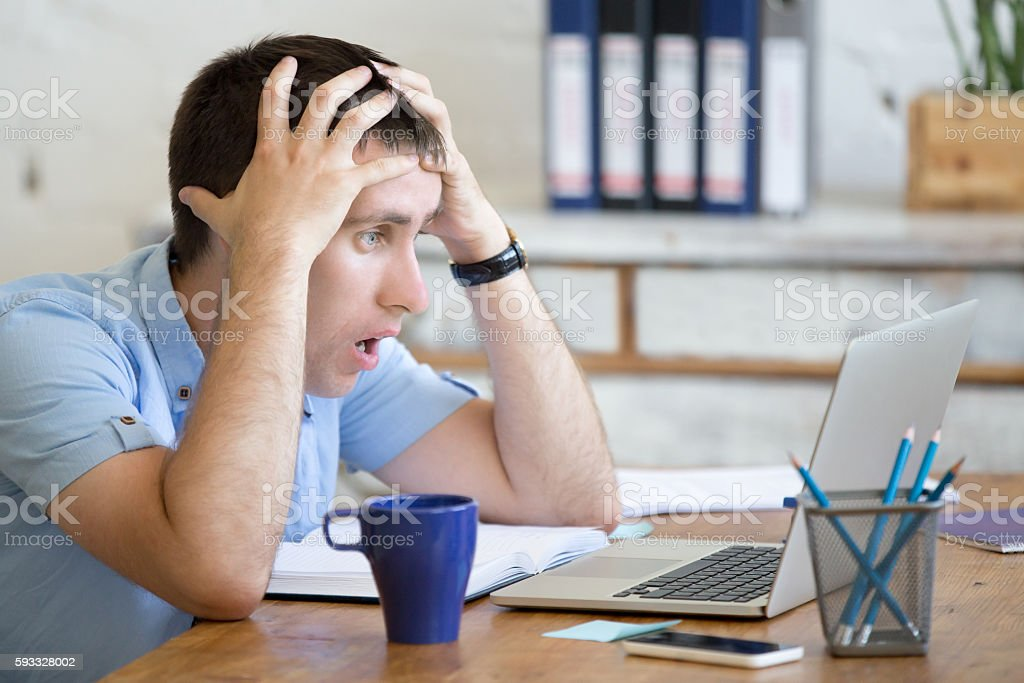 Young shocked office man looking at laptop computer stock photo